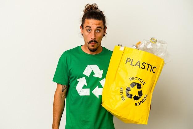 Jonge blanke man met lang haar recycling van plastic geïsoleerd op een witte achtergrond haalt schouders op en verwarde ogen.
