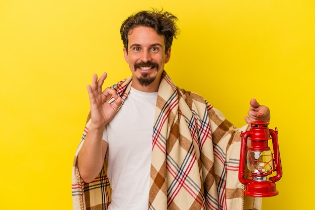 Jonge blanke man met lantaarn geïsoleerd op gele achtergrond vrolijk en zelfverzekerd met ok gebaar.