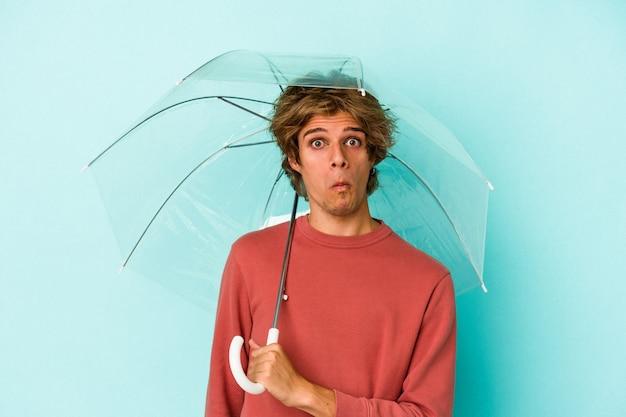 Jonge blanke man met make-up bedrijf paraplu geïsoleerd op blauwe achtergrond haalt schouders op en open ogen verward.