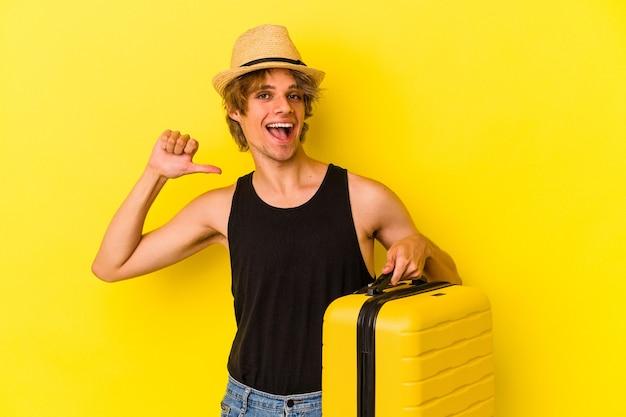 Jonge blanke man met make-up die geïsoleerd op een gele achtergrond gaat reizen, voelt zich trots en zelfverzekerd, een voorbeeld om te volgen.