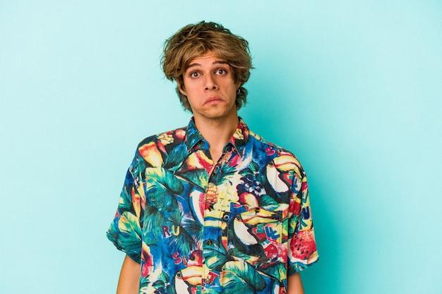 Jonge blanke man met make-up draagt een zomerkleren geïsoleerd op blauwe achtergrond haalt schouders op en open ogen verward.