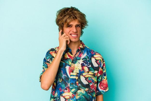 Jonge blanke man met make-up draagt een zomerkleren geïsoleerd op een blauwe achtergrond die oren bedekt met handen.