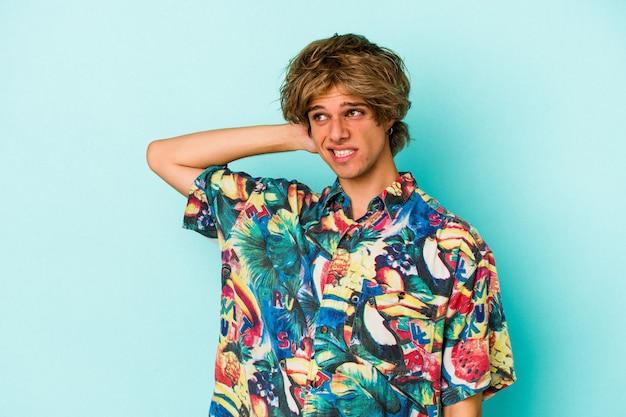 Jonge blanke man met make-up dragen van een zomerkleren geïsoleerd op blauwe achtergrond achterhoofd aanraken, denken en een keuze maken.