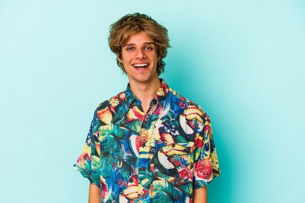 Jonge blanke man met make-up dragen van een zomerkleren geïsoleerd op blauwe achtergrond gelukkig, glimlachend en vrolijk.