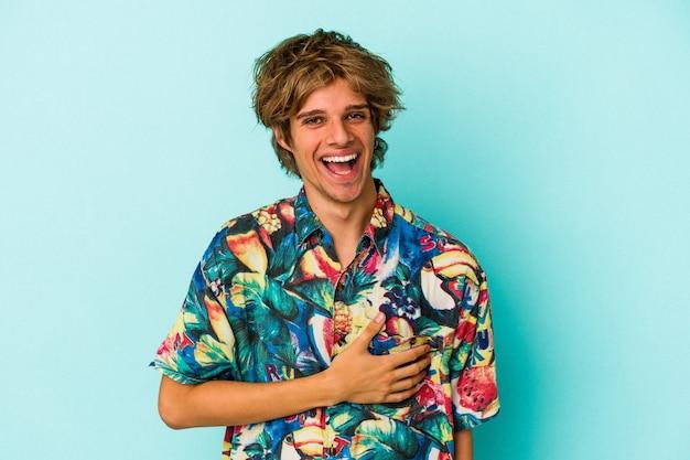 Jonge blanke man met make-up dragen van een zomerkleren geïsoleerd op blauwe achtergrond lachen en plezier hebben.