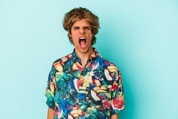 Jonge blanke man met make-up dragen van een zomerkleren geïsoleerd op blauwe achtergrond schreeuwen erg boos en agressief.