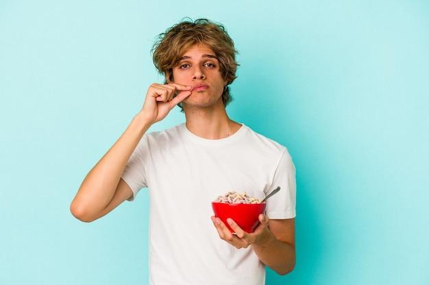 Jonge blanke man met make-up een kom met granen geïsoleerd op een blauwe achtergrond met vingers op de lippen die een geheim houden.