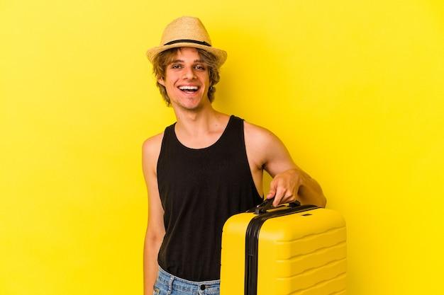 Jonge blanke man met make-up gaat reizen geïsoleerd op gele achtergrond gelukkig, glimlachend en vrolijk.