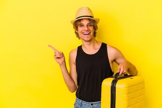 Jonge blanke man met make-up gaat reizen geïsoleerd op gele achtergrond glimlachend en opzij wijzend, met iets op lege ruimte.