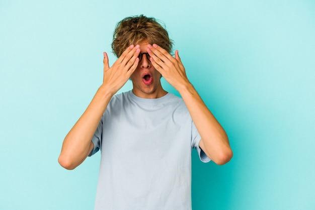 Jonge blanke man met make-up geïsoleerd op blauwe achtergrond bang voor ogen met handen.