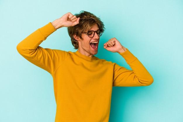 Jonge blanke man met make-up geïsoleerd op blauwe achtergrond die een speciale dag viert, springt en armen met energie opheft.