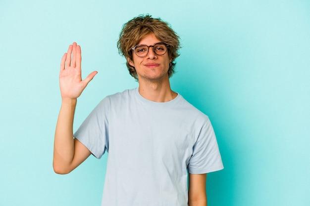 Jonge blanke man met make-up geïsoleerd op blauwe achtergrond glimlachend vrolijk met nummer vijf met vingers.