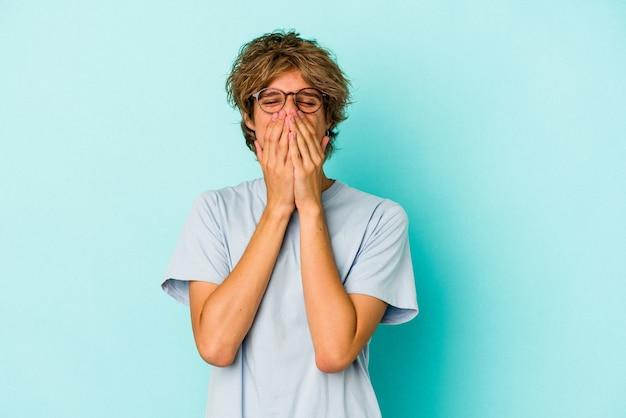 Jonge blanke man met make-up geïsoleerd op blauwe achtergrond lachen om iets, mond bedekken met handen.
