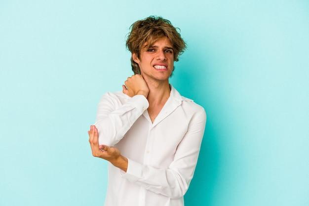 Jonge blanke man met make-up geïsoleerd op blauwe achtergrond masseren elleboog, lijden na een slechte beweging.