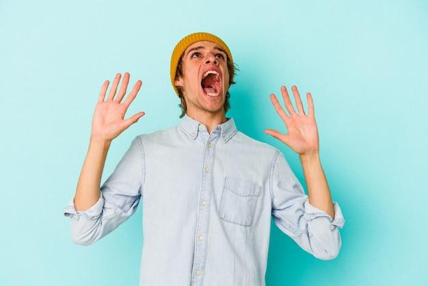 Jonge blanke man met make-up geïsoleerd op blauwe achtergrond schreeuwen naar de hemel, opzoeken, gefrustreerd.