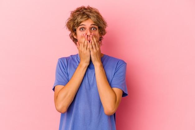 Jonge blanke man met make-up geïsoleerd op roze achtergrond geschokt, mond bedekken met handen, angstig om iets nieuws te ontdekken.