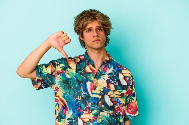 Jonge blanke man met make-up met een zomerkleren geïsoleerd op een blauwe achtergrond met een afkeergebaar, duim omlaag. onenigheid begrip.