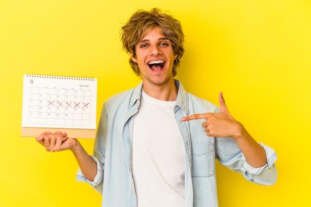 Jonge blanke man met make-up met kalender geïsoleerd op gele achtergrond persoon die met de hand wijst naar de ruimte van een shirtkopie, trots en zelfverzekerd