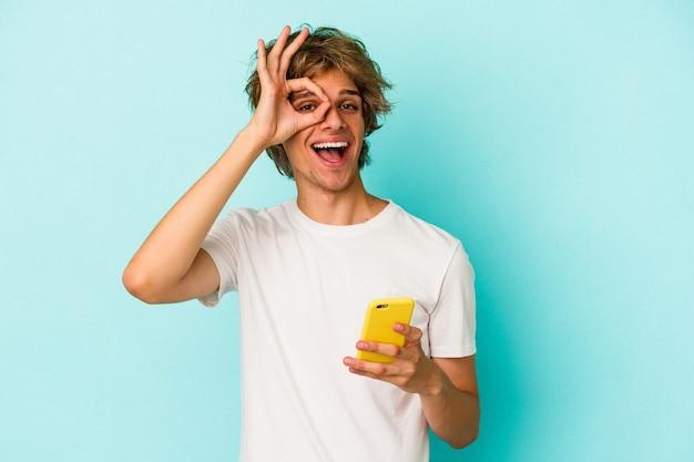 Jonge blanke man met make-up met mobiele telefoon geïsoleerd op blauwe achtergrond opgewonden houden ok gebaar in de gaten.