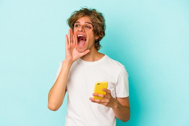 Jonge blanke man met make-up met mobiele telefoon geïsoleerd op blauwe achtergrond schreeuwen en palm in de buurt van geopende mond houden.