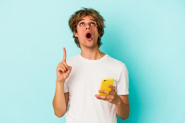 Jonge blanke man met make-up met mobiele telefoon geïsoleerd op blauwe achtergrond wijzend ondersteboven met geopende mond.