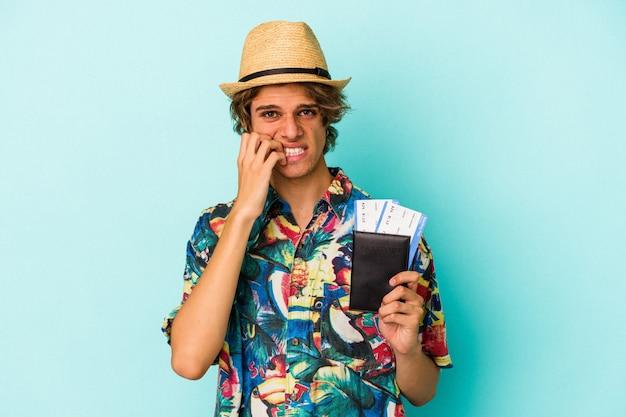 Jonge blanke man met make-up met paspoort geïsoleerd op blauwe achtergrond bijtende vingernagels, nerveus en erg angstig.