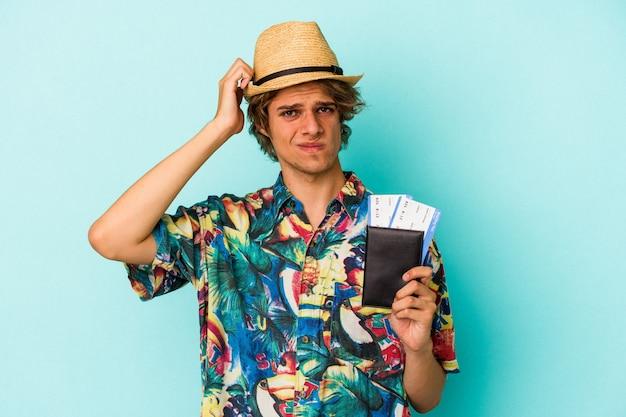 Jonge blanke man met make-up met paspoort geïsoleerd op blauwe achtergrond geschokt, ze heeft een belangrijke vergadering onthouden.
