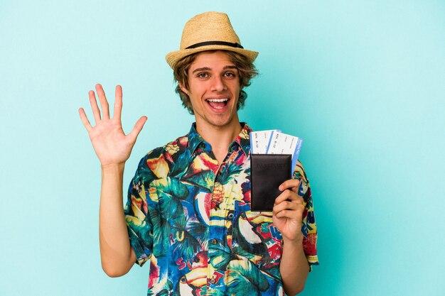 Jonge blanke man met make-up met paspoort geïsoleerd op blauwe achtergrond glimlachend vrolijk met nummer vijf met vingers.