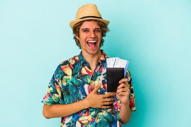 Jonge blanke man met make-up met paspoort geïsoleerd op blauwe achtergrond lachen en plezier hebben.