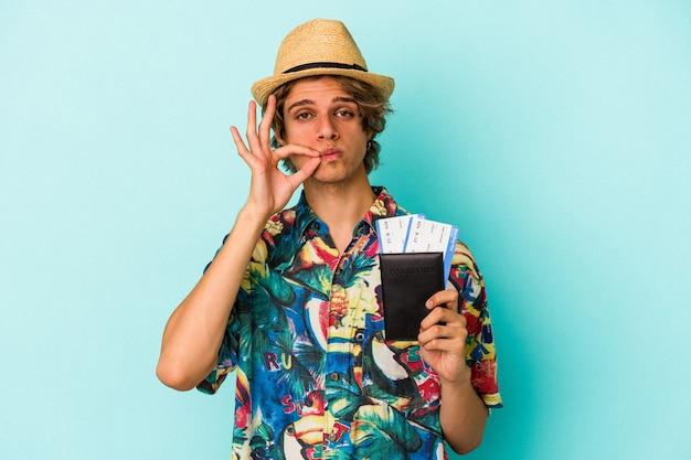Jonge blanke man met make-up met paspoort geïsoleerd op blauwe achtergrond met vingers op lippen die een geheim houden.