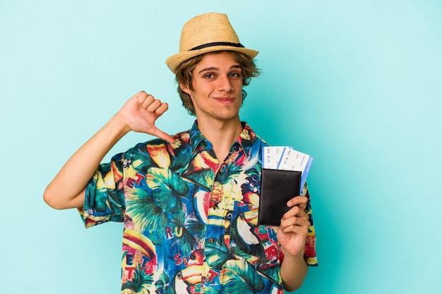 Jonge blanke man met make-up met paspoort geïsoleerd op blauwe achtergrond voelt zich trots en zelfverzekerd, voorbeeld om te volgen.
