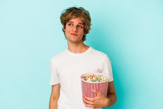 Jonge blanke man met make-up met popcorn geïsoleerd op blauwe achtergrond, dromend van het bereiken van doelen en doeleinden