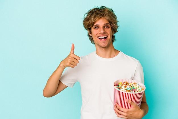 Jonge blanke man met make-up met popcorn geïsoleerd op blauwe achtergrond glimlachend en duim omhoog