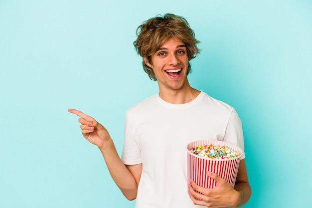 Jonge blanke man met make-up met popcorn geïsoleerd op blauwe achtergrond glimlachend en opzij wijzend, iets tonend op lege ruimte.