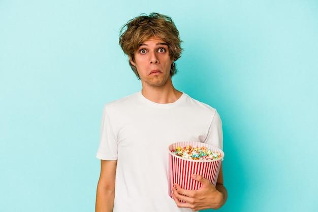 Jonge blanke man met make-up met popcorn geïsoleerd op blauwe achtergrond haalt zijn schouders op en verwarde ogen.