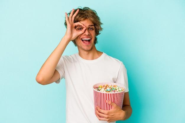 Jonge blanke man met make-up met popcorn geïsoleerd op blauwe achtergrond opgewonden houden ok gebaar in de gaten.