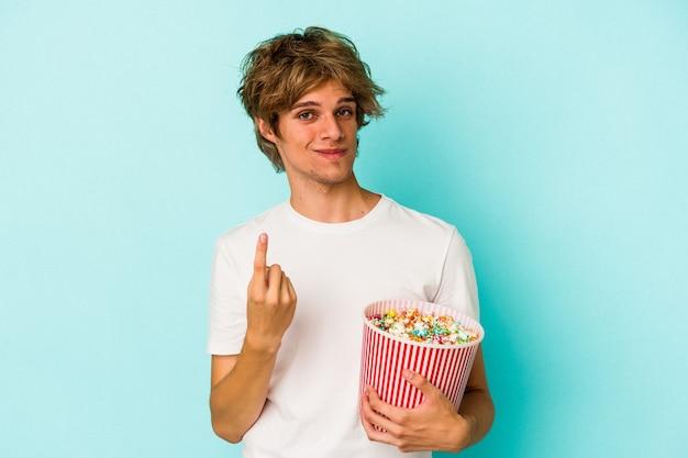 Jonge blanke man met make-up met popcorn geïsoleerd op blauwe achtergrond wijzend met de vinger naar je alsof uitnodigend dichterbij komt.