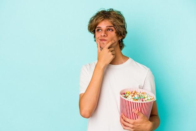 Jonge blanke man met make-up met popcorn geïsoleerd op blauwe achtergrond zijwaarts kijkend met twijfelachtige en sceptische uitdrukking.