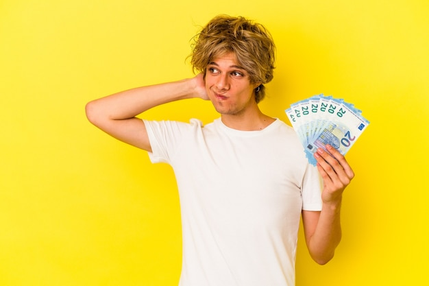 Jonge blanke man met make-up met rekeningen geïsoleerd op een gele achtergrond die de achterkant van het hoofd aanraakt, denkt en een keuze maakt.