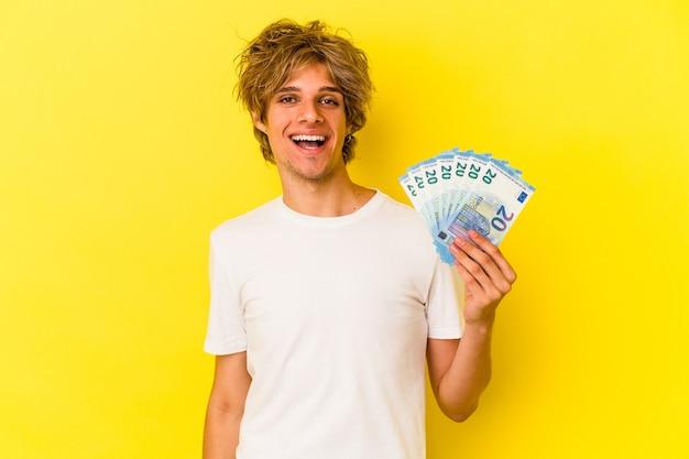 Jonge blanke man met make-up met rekeningen geïsoleerd op gele achtergrond gelukkig, glimlachend en vrolijk.