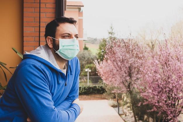 Jonge blanke man met masker uitkijken op het terras van het huis tijdens de quarantaine vanwege de pandemie van covid19 coronavirus.