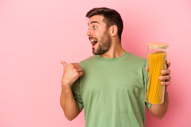 Jonge blanke man met pasta pot geïsoleerd op roze achtergrond punten met duim vinger weg, lachen en zorgeloos.