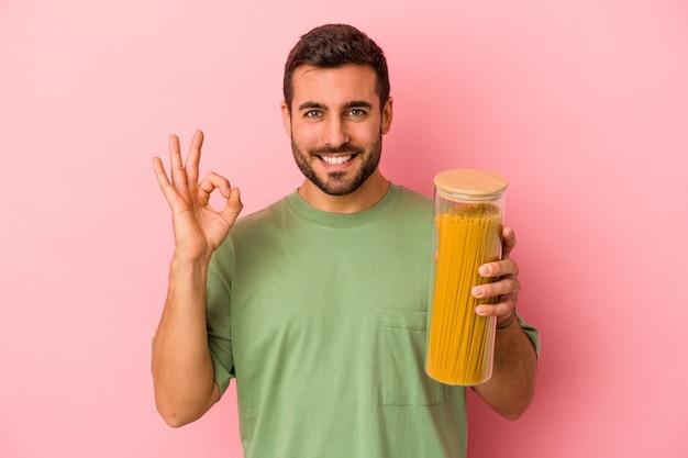 Jonge blanke man met pasta pot geïsoleerd op roze achtergrond vrolijk en zelfverzekerd tonen ok gebaar.