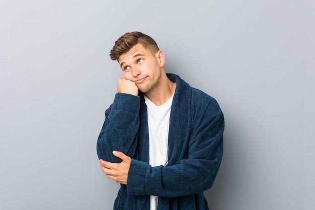 Jonge blanke man met pyjama die zich verdrietig en peinzend voelt, kijkend naar lege ruimte.