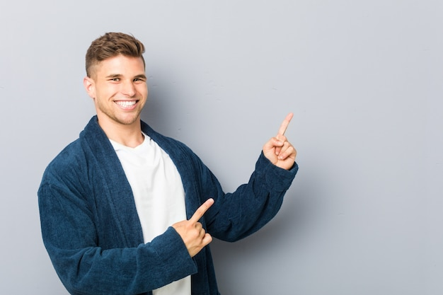 Jonge blanke man met pyjama wijzend met wijsvingers op een kopie ruimte, uiting van opwinding en verlangen.