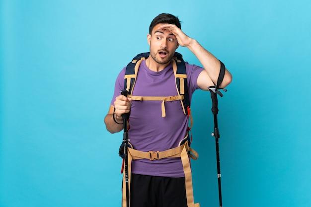 Jonge blanke man met rugzak en wandelstokken geïsoleerd op blauwe achtergrond doet verrassingsgebaar tijdens het kijken naar de zijkant