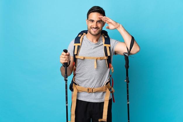 Jonge blanke man met rugzak en wandelstokken geïsoleerd op blauwe achtergrond groeten met hand met gelukkige uitdrukking