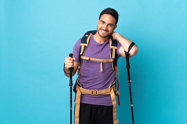 Jonge blanke man met rugzak en wandelstokken geïsoleerd op blauwe achtergrond lachen