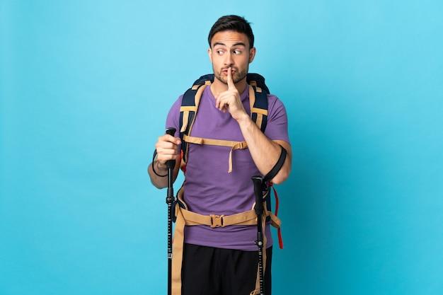 Jonge blanke man met rugzak en wandelstokken geïsoleerd op blauwe achtergrond met een teken van stilte gebaar vinger in de mond steken
