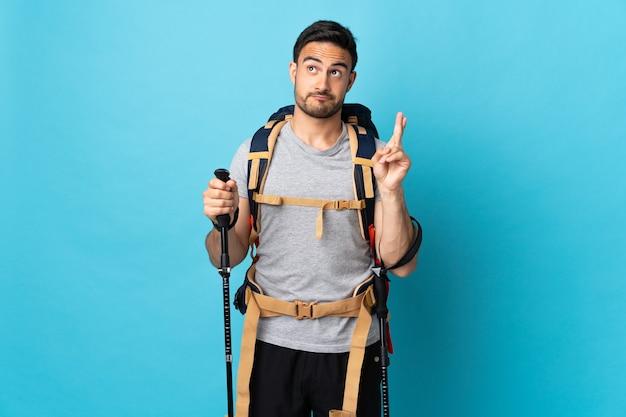Jonge blanke man met rugzak en wandelstokken geïsoleerd op blauwe achtergrond met vingers kruisen en het beste wensen